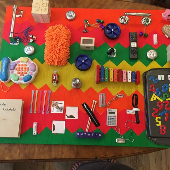 What an amazing busy board she made for her twins!  Love this DIY sensory board - LOTS of fun things for toddlers to play with